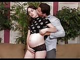Sexy zwangere brunette tiener op een sofa